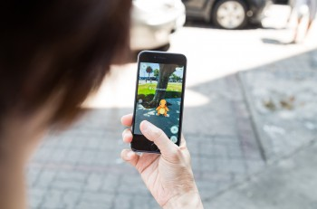 KUALA LUMPUR MALAYSIA JULY 16 2016: An IOS user plays Pokemon Go a free-to-play augmented reality mobile game developed by Niantic for iOS and Android devices.