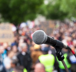 Microphone in focus against blurred crowd. Political rally.