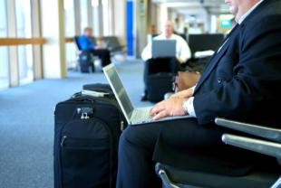 An image of a business man on his laptop in the airport while waiting for his flight