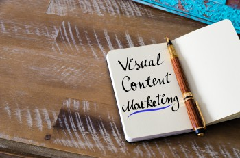 Retro effect and toned image of notebook next to a fountain pen. Business concept image with handwritten text VISUAL CONTENT MARKETING copy space available