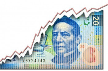 Growth graph growing through a Mexican peso bill.