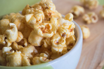 sweet caramel popcorn with bowl full of sweet caramel popcorn.