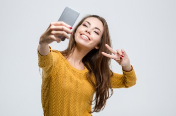 Portrait of a smiling cute woman making selfie photo on smartpho