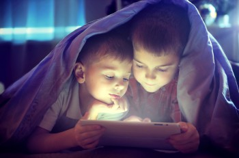 Two kids using tablet pc under blanket at night. Brothers with t