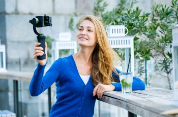 Young pretty woman broadcast live video using action camera and gimbal