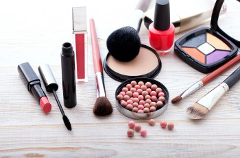 Makeup cosmetics products on white wooden background with copy space. Cosmetics make up artist objects: lipstick, eye shadows, eyeliner, concealer, nail polish, powder, tools for make-up