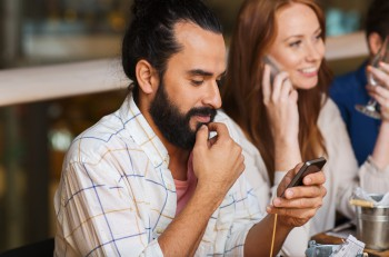leisure, technology, lifestyle and people concept - happy friends with smartphones calling and texting at dinner in restaurant