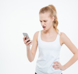 Angry casual woman using smartphone isolated on a white background