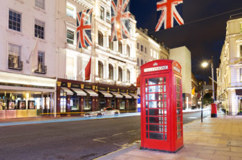 United Kingdom England London - 2016 June 17: Popular tourist Red phone booth with flags union jack in night lights illumination