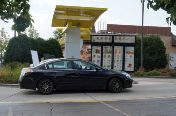 NAPERVILLE, ILLINOIS / UNITED STATES - JULY 23, 2015: Motorists use the drive-through service to purchase food at the McDonald's Restaurant in Naperville.