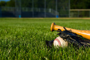 a baseball, glove and bat on a baseball diamond.