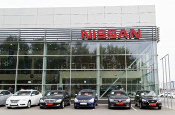 Ulyanovsk Russia - July 20 2016: Building of Nissan car selling and service center with Nissan sign. In front of the standing cars for sale.