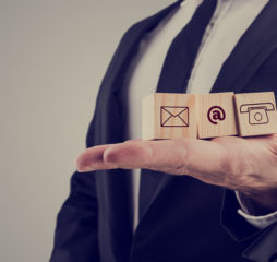 Retro style image of a businessman holding three wooden cubes with contact symbols - envelope at sign and telephone - conceptual of communication and business support.