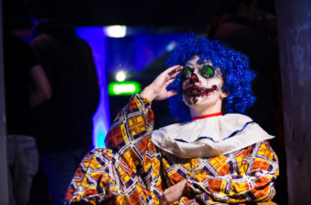 Crazy ugly grunge evil clown in town on Halloween making people shock and scared. Crazy ugly grunge evil clown. Scary professional Halloween masks. Halloween party
