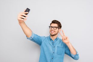 Happy Man In Glasses Making Selfie On Smartphone And Showing Two
