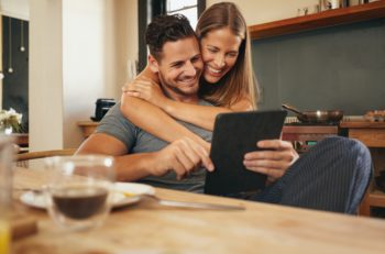Couple smiling as they read a tablet computer together in morning in the kitchen. Young man and woman catching up on social media smiling. Woman hugging her boyfriend holding tablet PC. ** Note: Soft Focus at 100%, best at smaller sizes
