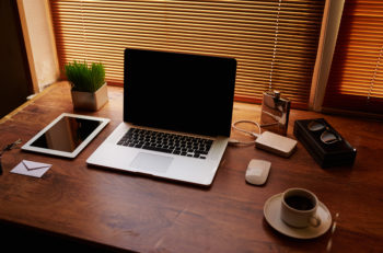 Laptop computer and digital tablet with copy space screen mouse plant pot cup of coffee empty touch pad business person workstation