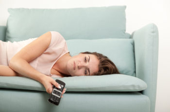 Sleepy young woman lying on couch holding TV remote control casual style indoor shoot