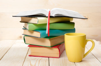 Stack of colorful books, open book and cup on wooden table. Back