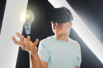 3d technology, virtual reality, entertainment and people concept - close up of happy young man with virtual reality headset or 3d glasses playing game and holding light bulb projection