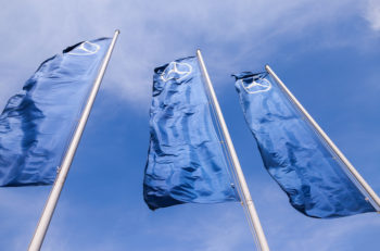 TOGLIATTI RUSSIA - MAY 3 2015: The flags of Mercedes-Benz over blue sky. Mercedes-Benz is a German automobile manufacturer