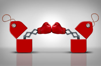 Price fight and commercial competition as a business concept for cutting retail prices to compete for customer loyalty as two open sales tags with boxing gloves punching each other for market supremecy.