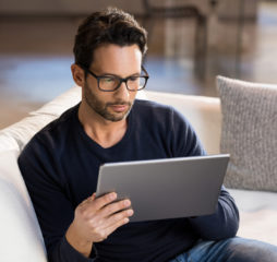 Man using digital tablet on sofa at home. Portrait of a serious man wearing eyeglasses working on digital tablet at home. Handsome man sitting on the sofa using tablet pc at home in the living room.