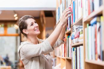 Woman choosing book in bookstore