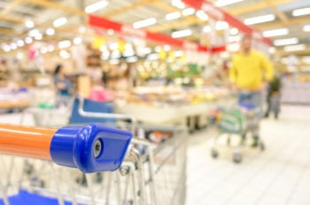 Blurred defocused grocery supermarket - Consumerism concept in period of economic crisis - Bright vivid blur of people in commercial center - Shallow depth of field with focus on shopping cart edge