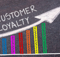 CUSTOMER LOYALTY written with chalk on tarmac over colorful graph and rising arrow business marketing and creativity concept