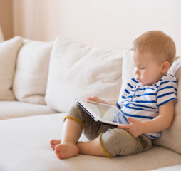 Adorable blond toddler boy laying on the sofa and playing with tablet pc at home indoors. Child with tablet computer.