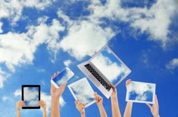 Hands holding electronic gadgets with sky on screens. Cloud comp