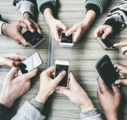 Group of friends having fun together with smartphones - Closeup of hands social networking with mobile phones - Technology and phone addiction concept - Soft focus on bottom hands - Vintage filter