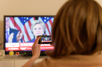 PARIS FRANCE - NOV 9 2016: Woman watching tv news on EURONEWS Channel for Hillary Clinton speech after loosing to Donald J Trump - the result elections in the United States where Donald J Trump has become the 45th president of USA