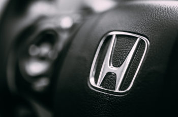 Borgund, Norway - August 1, 2014: Honda Black Steering Wheel And Silver Logo. Honda Motor Co., Ltd. is a Japanese public multinational conglomerate corporation.