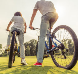 Back and low angle view of handsome young dad and his little son in casual clothes riding bikes in park