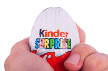 ISTANBUL TURKEY - MARCH 8 2015 : Kinder Surprise chocolate egg holding on hand with a small toy inside manufactured by Ferrero isolated on white back ground.