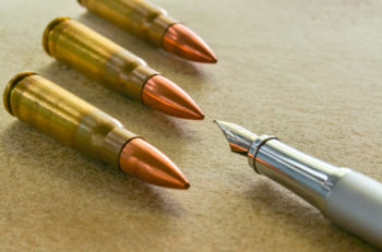Silver fountain pen and three bullets arranged in the corners of the image