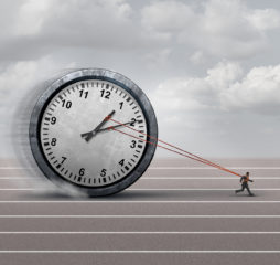 Time burden business concept as a burdened businessman or employee pulling a heavy clock as a symbol for deadline stress or schedule pressure and an icon for aging.