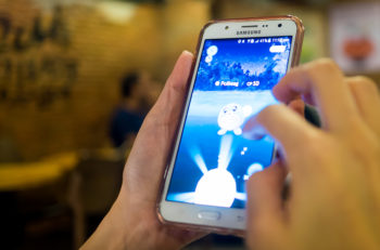 Bangkok, Thailand - August 6, 2016: A girl is playing Pokemon Go on her samsung mobile in a restaurant.