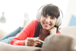 Smiling young woman relaxing at home on the couch she is wearing headphones using a digital tablet and watching a streaming video