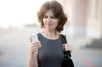 Portrait of stressed office young woman holding cellphone in hands on the city street in summer looking at screen with cross face expression mad at stressful texts and calls