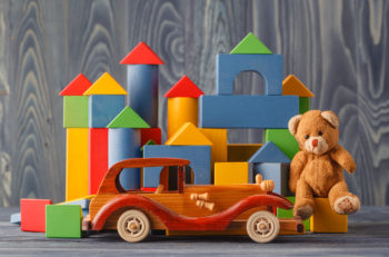 House made of wooden blocks to assemble near a toy and a wooden toy car