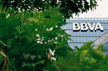 Tower of BBVA bank behind branches with green leaves of a tree at downtown of Buenos Aires, Argentina. May 31, 2016