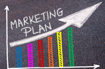 MARKETING PLAN written with chalk on tarmac over colorful graph and rising arrow business marketing and creativity concept