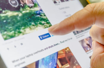 Bangkok Thailand - June 17 2015 : Unidentified human finger touch on 'Facebook' button for share the news on the internet website to his or her owner Facebook feed