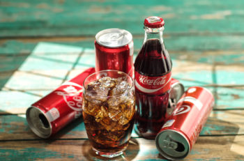 MINSK BELARUS-AUGUST 26 2016: Glass of Coca-Cola with ice can and bottle of Coca-Cola on wooden background. Coca-Cola is a carbonated soft drink sold in stores throughout the world.