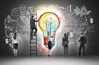 Rear view of business team near blackboard with colorful light bulb and startup sketch drawn on it. Concept of idea of business