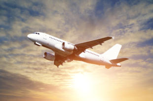 Airplane closeup - travel background with airplane flying in the colored sunny sky. White flying airplane in the sunlight - closeup of flying airplane with blank livery.Airplane in the flight