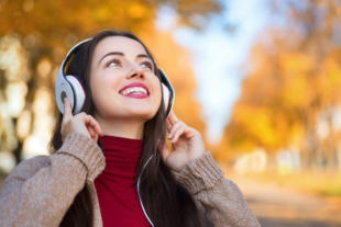Young happy smiling brunette woman with headphones outdoors on autumn day. Girl listening music in headphones in autumn park. Portrait of woman at outdoor with headphones. Autumn portrait of happy girl. Copy space